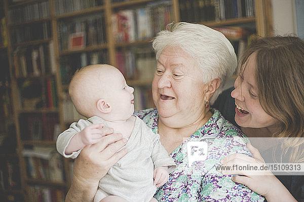 Glückliche Großmutter mit Mutter  die ein kleines Mädchen hält