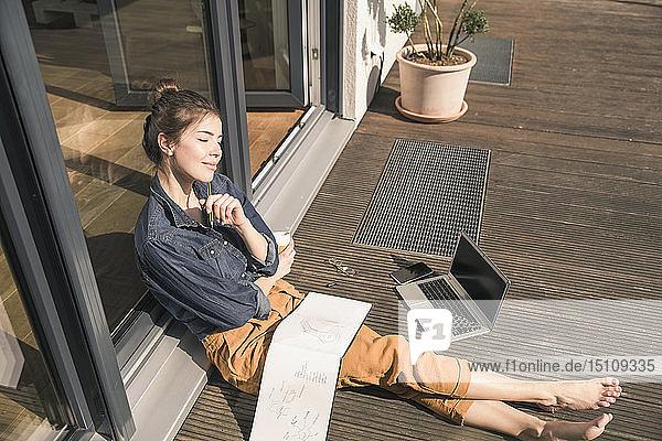 Junge Frau mit geschlossenen Augen sitzt zu Hause auf der Terrasse mit Laptop und Buch