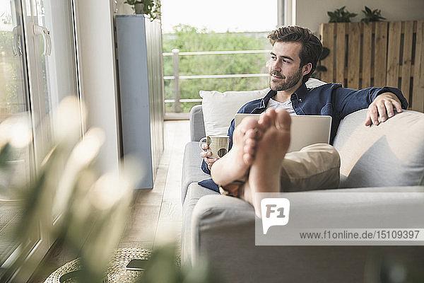 Jung und auf der Couch sitzend  Laptop benutzen  Kaffee trinken