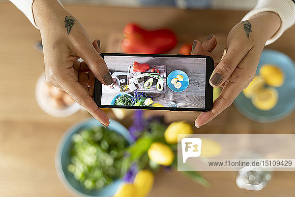 Woman's hands holding smartphone  taking picture of vegetables