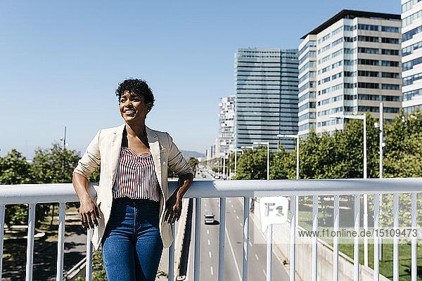 Lächelnde Geschäftsfrau  die sich an ein Brückengeländer lehnt  im Hintergrund Bürogebäude