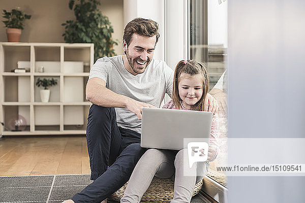 Young man and little girl surfing the net together