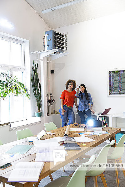Two women discussing in modern office with video projector on table
