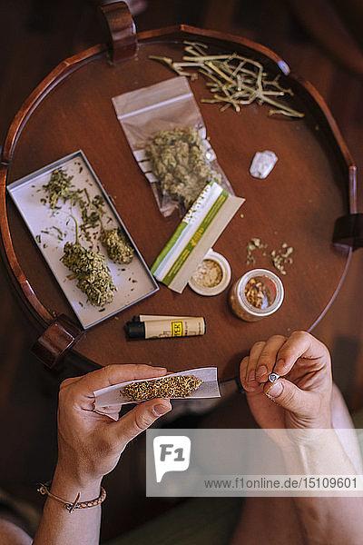Nahaufnahme einer Hand  die von oben einen Joint Marihuana rollt