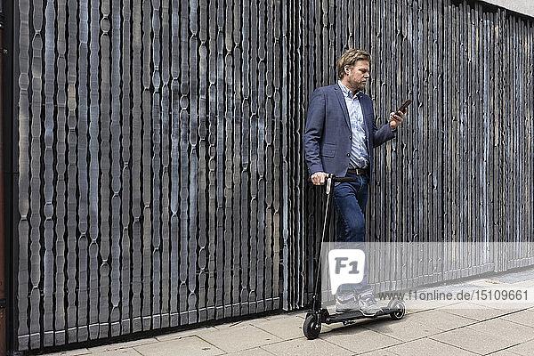Geschäftsmann steht auf Bürgersteig mit E-Scooter und schaut auf Handy