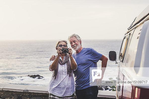 Älteres Ehepaar reist in einem Oldtimer-Van und fotografiert am Meer