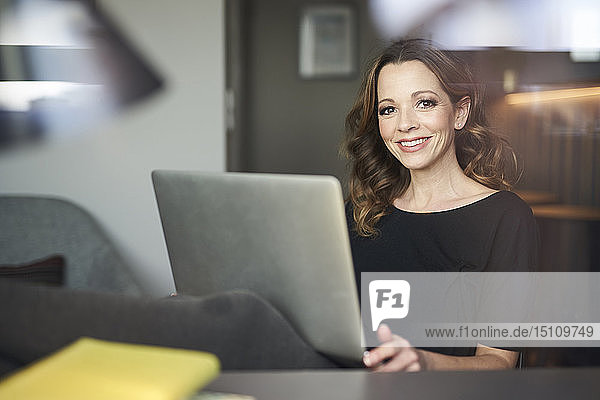 Porträt einer lächelnden Frau mit Laptop hinter einer Fensterscheibe