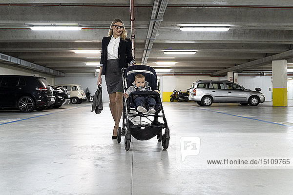 Young businesswoman pushing stroller with baby boy in car park