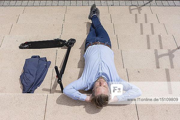 Geschäftsmann mit E-Scooter entspannt sich auf einer Treppe
