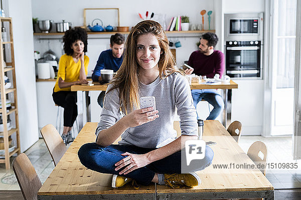 Woman with cell phone sitting on dining table at home with friends in background