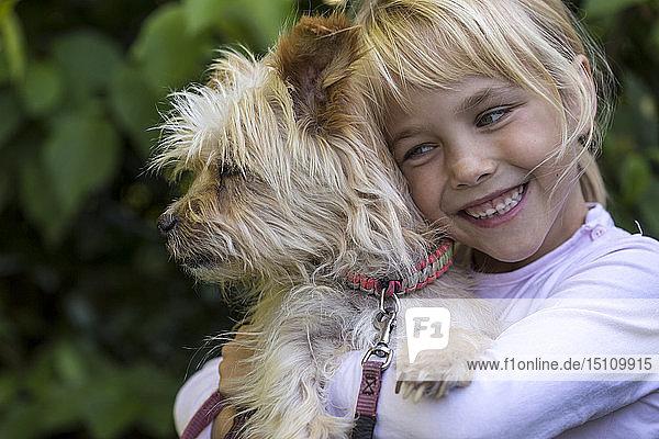 Portrait of happy little girl cuddling her dog