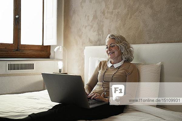 Porträt einer inhaltlich reifen Geschäftsfrau  die am Bett sitzt und am Laptop arbeitet