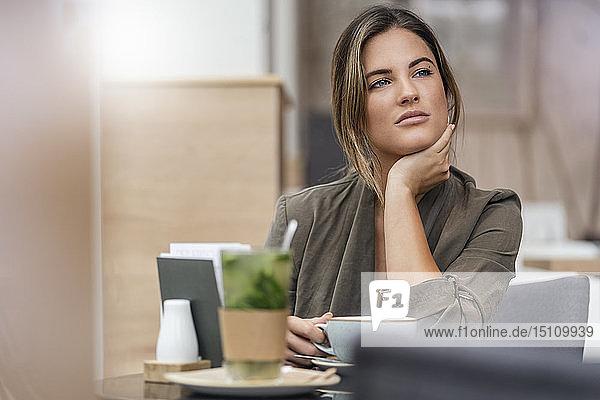 Junge Geschäftsfrau mit Kaffeetasse in einem Café  durch ein Fenster gesehen