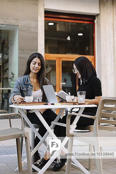 Zwei Freunde sitzen mit Buch und Laptop in einem Straßencafé zusammen
