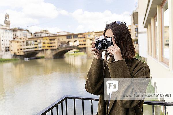 Italien  Florenz  junge Touristin beim Fotografieren in Ponte Vecchio