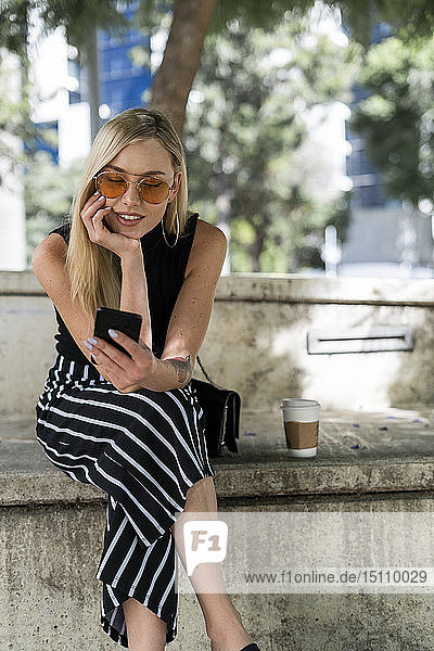 Blonde junge Frau sitzt mit ihrem Handy an einer Wand
