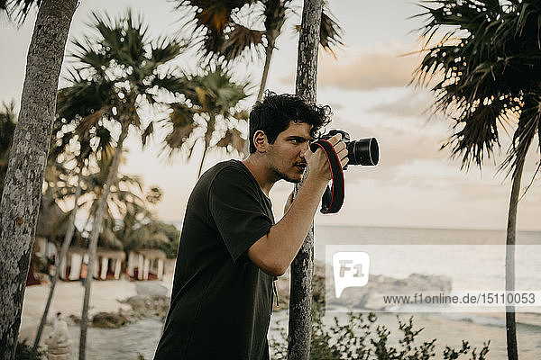 Mexico,  Quintana Roo,  Tulum,  young man taking pictures on the beach