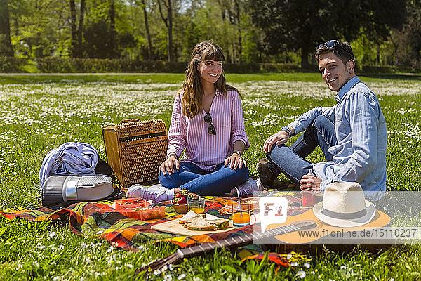 Junges Paar beim Picknick mit gesundem Essen in einem Park