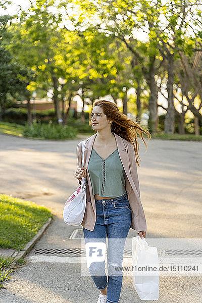 Junge rothaarige Frau mit Einkaufstaschen in einem Park