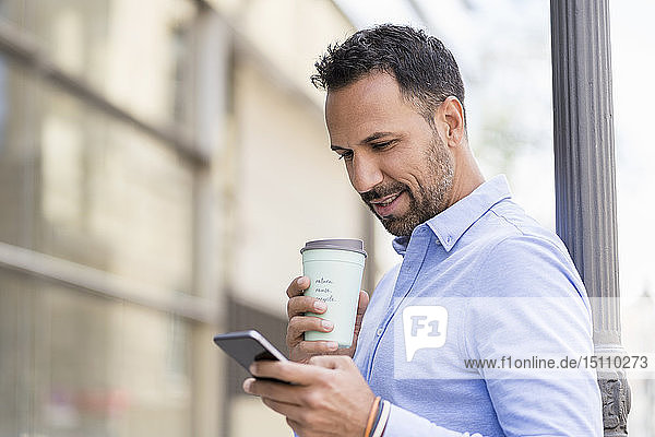 Businessman with with takeaway coffee and cell phone in the city
