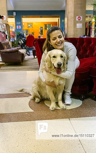 Smiling woman hugging dogh in a vintage shop