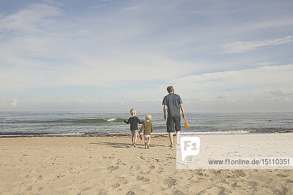 Father with two kids on the beach