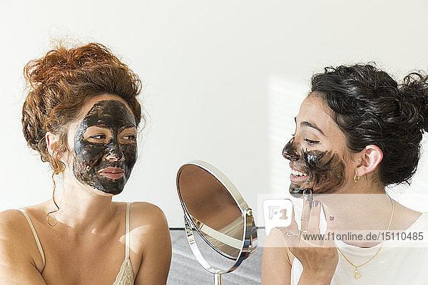 Zwei glückliche junge Frauen tragen zu Hause Gesichtsmasken auf