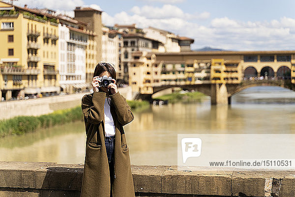 Italy  Florence  young tourist woman taking pictures at Ponte Vecchio