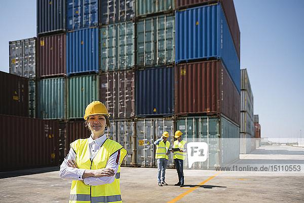 Porträt einer selbstbewussten Arbeitnehmerin vor Kollegen und Frachtcontainern auf einem Industriegelände