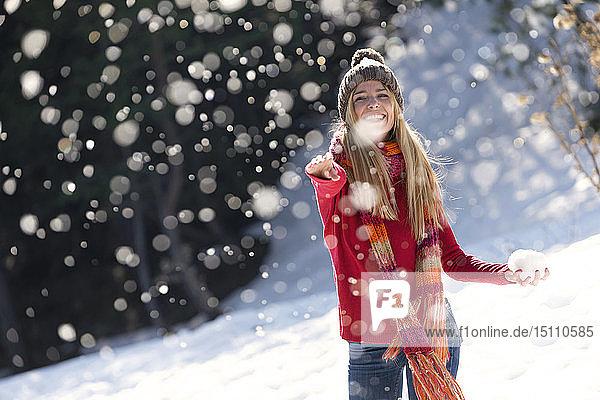 Junge blonde Frau wirft im Winter mit Schnee