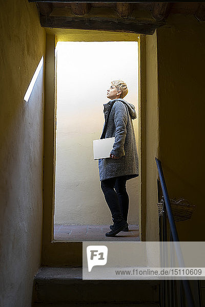 Young woman with digital tablet looking up