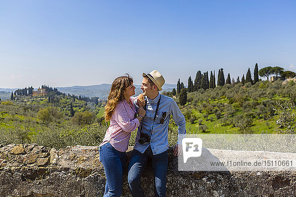 Young couple embracing at wall in Florence  Tuscany  Italy