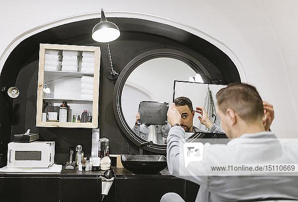Customer checking his haircut in mirror at barber shop
