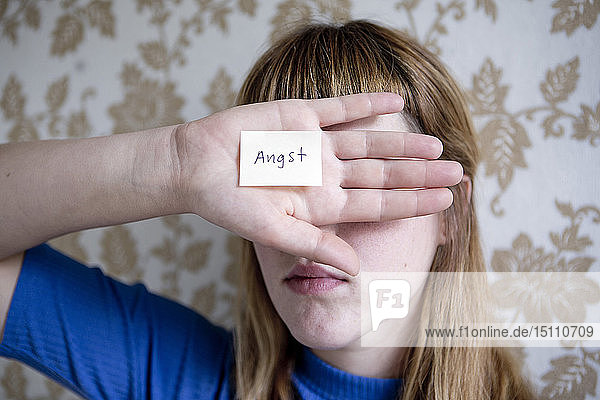 Die Studentin zeigt ihre Hand  eine Notiz mit dem Wort Angst auf der Hand