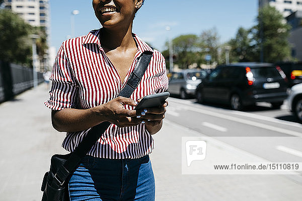 Woman using smartphone while walking in the city