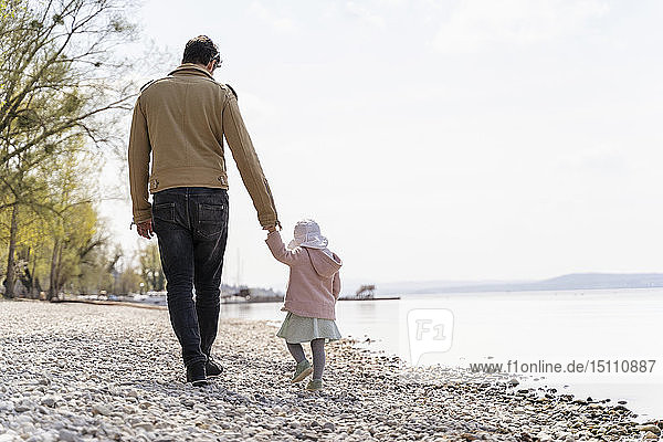 Germany  Bavaria  Herrsching  father and daughter walking on pebble beach at lakeshore