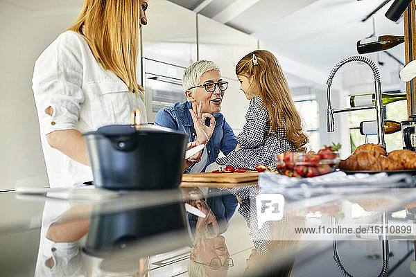Mother  daughter and grandmother having fun  chopping strawberries in the kitchen
