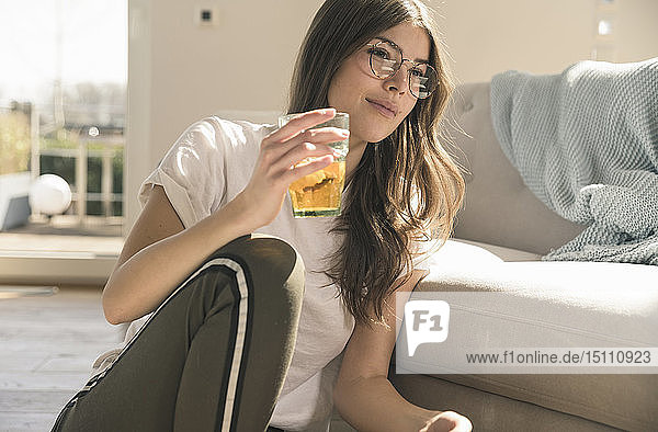 Young woman sitting on the floor at home with a drink