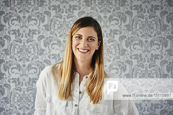 Porträt einer glücklichen  blonden Frau vor einer gemusterten Tapete