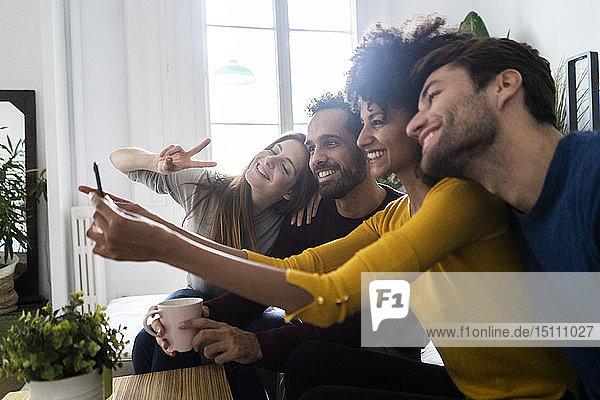 Vier glückliche Freunde sitzen auf der Couch und machen ein Selfie