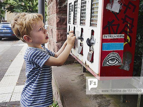 Unglücklicher kleiner Junge am Kaugummiautomaten