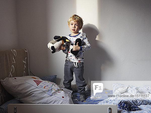 Porträt eines kleinen Jungen  der mit seinen Plüschtieren auf dem Bett steht