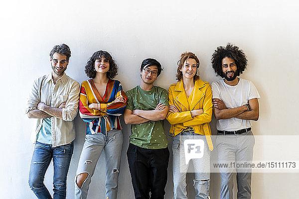 Porträt einer selbstbewussten Gruppe von Freunden  die an einer Wand stehen