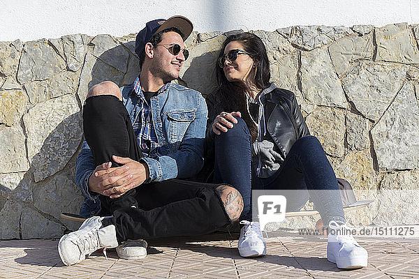 Junges verliebtes Paar sitzt Seite an Seite auf einem Longboard
