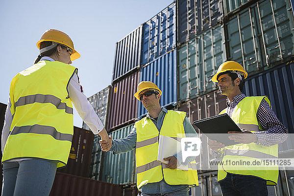 Arbeiter schütteln Hände vor Frachtcontainern auf einem Industriegelände