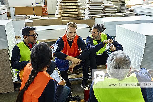 Beschäftigte in der Fabrik machen gemeinsam Mittagspause