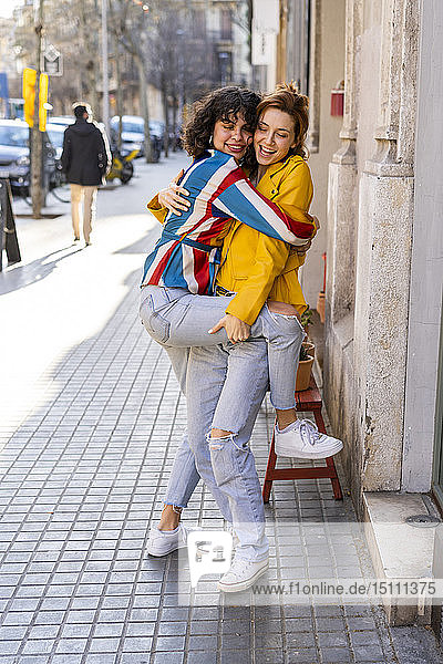Zwei unbekümmerte junge Frauen umarmen sich in der Stadt