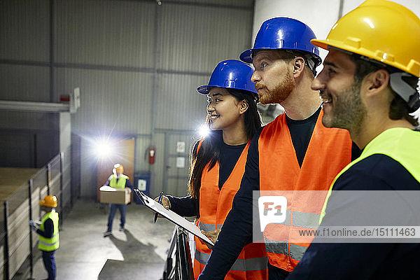 Zwei Männer und eine lächelnde Frau in reflektierenden Westen in der Fabrik