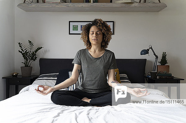 Woman practicing yoga  sitting on bed  meditating