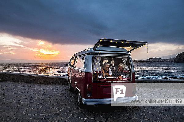 Älteres Ehepaar reist in einem Oldtimer-Van und liegt im Kofferraum
